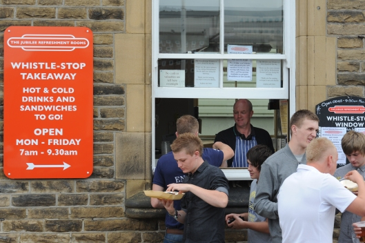 Chris Wright serves food from the 'hatch' during the annual rushbearing festival. The window is used to sell food & drink to hungry commuters every morning before the rooms open.