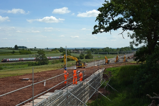 Building a retaining wall to protect an old Marl pit which is being preserved. The area above at the top of the embankment is being levelled as it will contain a drainage channel. meanwhile, in the background, Pendolinos pass on the existing WCML.