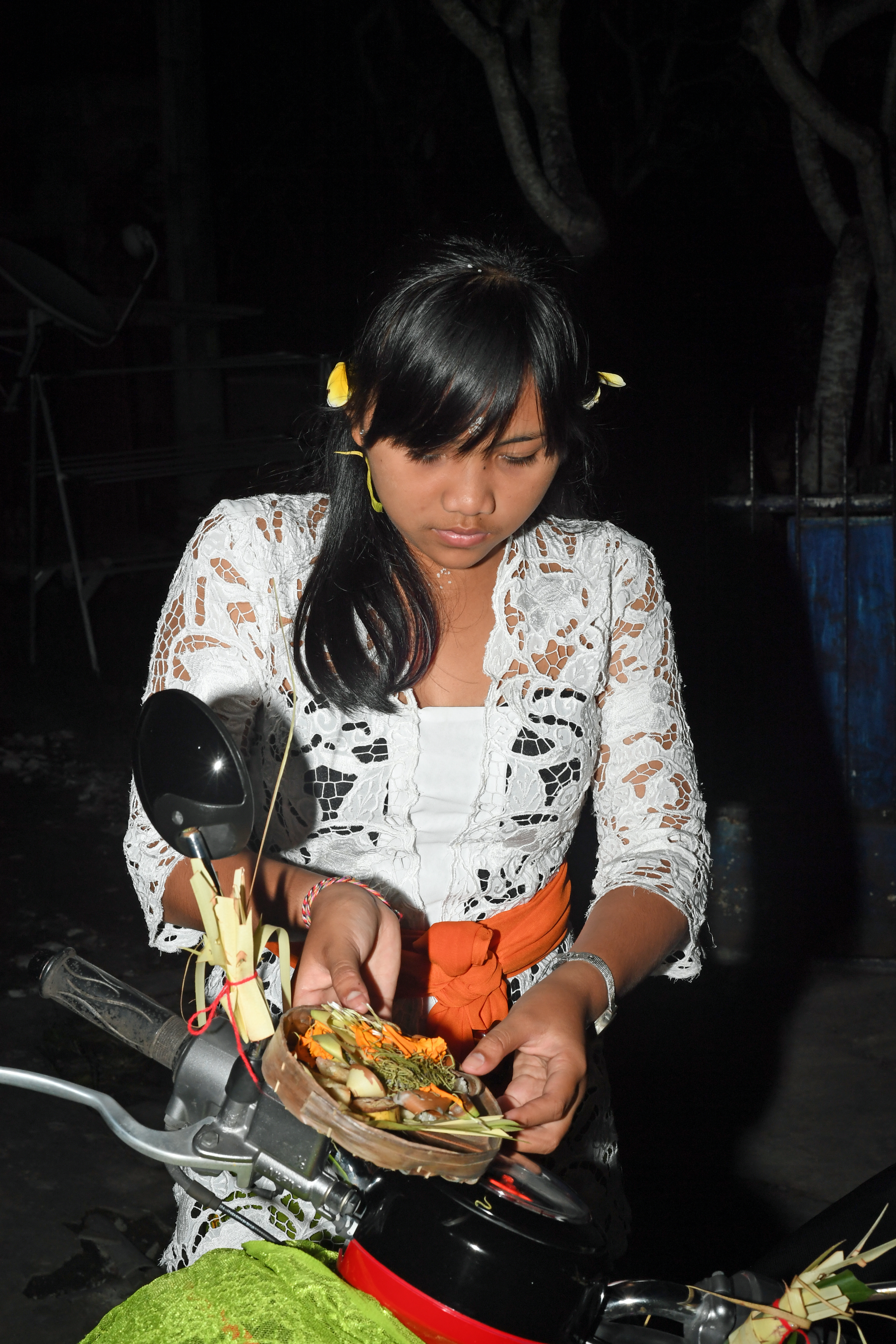 DG264162. Girl placing blessings on a scooter during . Tumpak Lendep. Ubud. Bali. Indonesia. 4.2.17.JPG