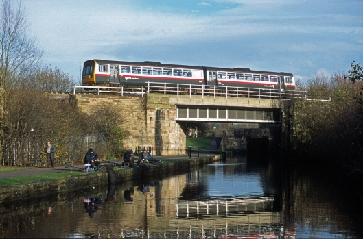 11551. FNW Class 142 passes over the Leeds and Liverpool canal. Wigan. 28.11.2002